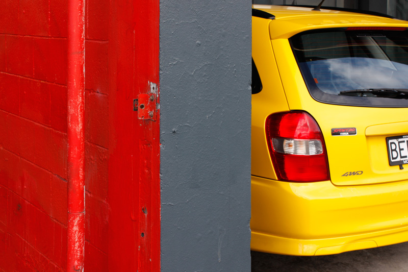 red-wall-yellow-car